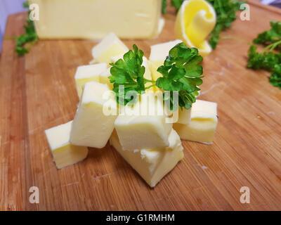 Pile de cubes de beurre frais, jaune, sur une planche à découper en bois Banque D'Images