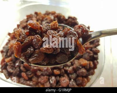Brown raisins secs sur une cuillère, en face de plus de raisins secs Banque D'Images