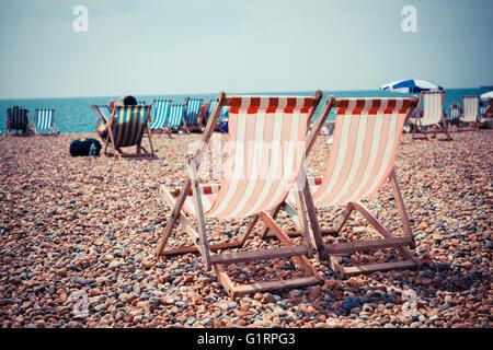Deux chaises longues sur une plage de galets Banque D'Images