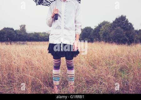 Une jeune femme avec un parapluie est debout dans un champ Banque D'Images