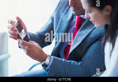 Businessman showing cell phone vidéo pour businesswoman