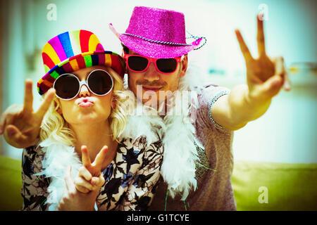 Portrait playful couple en costume lunettes de soleil et chapeaux gesturing peace sign Banque D'Images