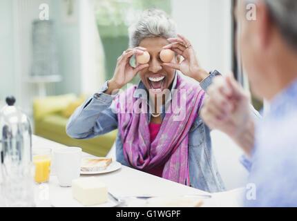 Femme mature ludique couvrant les yeux avec les oeufs de table de petit déjeuner Banque D'Images