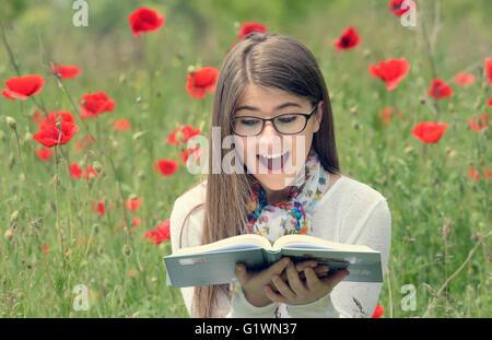 Teenage girl lire un livre en champ de coquelicots Banque D'Images