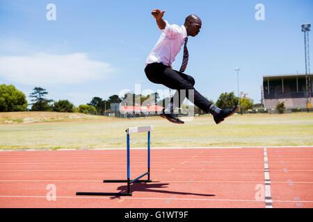 Businessman jumping un obstacle lors de l'exécution Banque D'Images