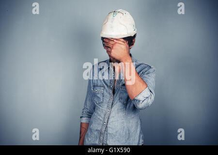 Un col bleu portant un casque est couvrant son visage avec ses mains Banque D'Images