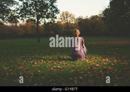 Une jeune femme est de l'emplacement sur l'herbe dans le parc le soir Banque D'Images
