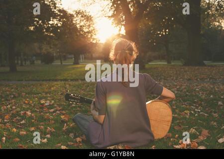 Vue arrière du jeune femme assise sur l'herbe et jouer de la guitare dans le parc au coucher du soleil Banque D'Images