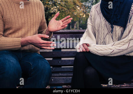 Un jeune homme et femme sont assis sur un banc de parc et à discuter Banque D'Images
