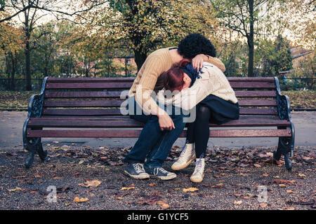 Un jeune couple est triste embrassant sur un banc de parc en automne Banque D'Images