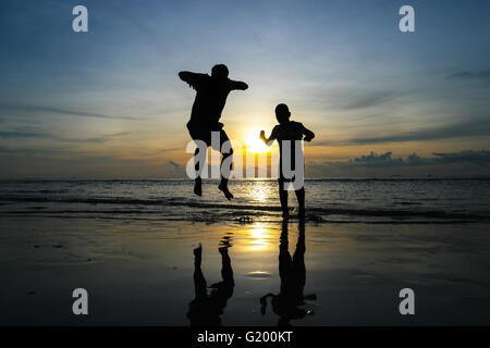 Les garçons de sauter sur la plage Coucher du Soleil Banque D'Images