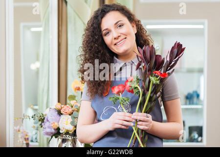 Magnifique Portrait de femme bouclés debout dans le magasin de fleurs fleuriste Banque D'Images