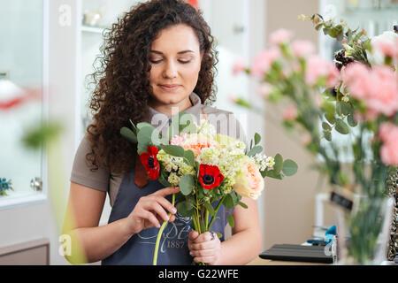 Thoughtful young woman holding Flowers fleuriste bouquet et faire en boutique Banque D'Images