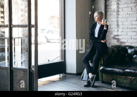 Belle fille blonde tenant un verre de whisky dans un bar et en attente de quelqu'un Banque D'Images