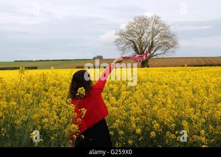 Woman waving foulard en champ de colza, Niort, France Banque D'Images