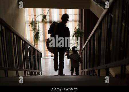 Père et fils descendant des escaliers holding hands Banque D'Images