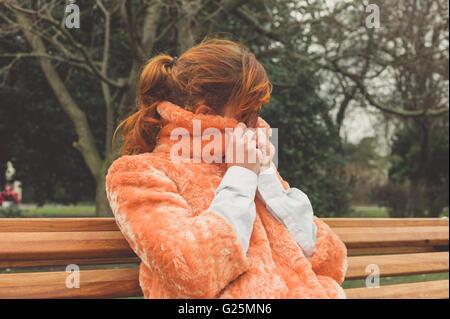 Une jeune femme est assise sur un banc de parc et s'enroule dans son manteau, un jour d'hiver Banque D'Images