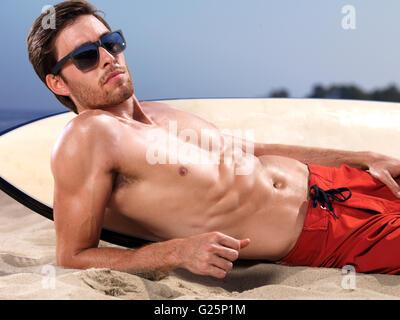 Un homme portant des shorts de couché à côté d'une planche dans le sable Banque D'Images