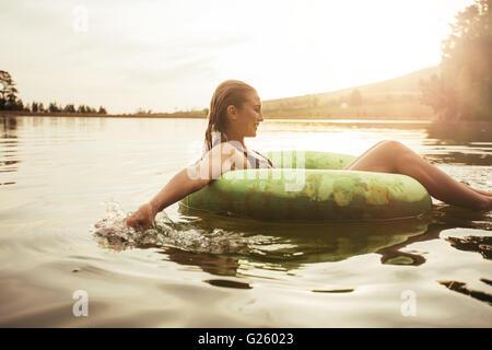 Side portrait of happy young woman in lake sur anneau gonflable. Jeune fille se détendre dans l'eau un jour d'été. Banque D'Images
