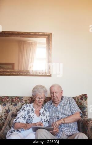 Piscine verticale tourné de couple de retraités à la maison à l'aide de tablette numérique. Young man and woman Banque D'Images