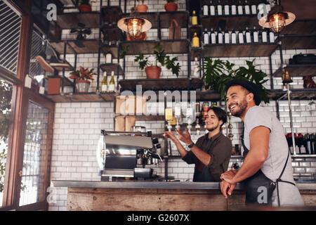 Café workers standing au guichet à l'extérieur du café et le sourire. Banque D'Images