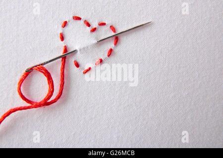 Coeur rouge brodé sur un drap blanc close up. Concept passion pour la couture et broderie. Composition horizontale.vue Banque D'Images