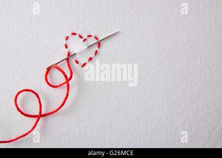 Coeur rouge brodé sur un linge blanc. Concept passion pour la couture et broderie. Composition horizontale.vue d'en Banque D'Images