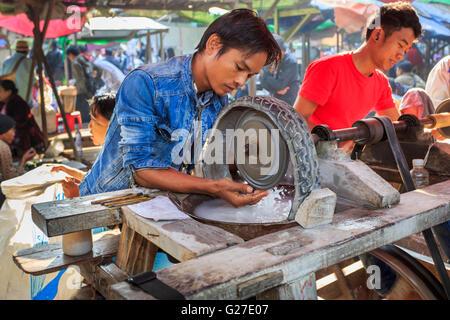 Les jeunes artisans locaux travaillant à jade avec une roue de polissage dans le marché de Jade, Mandalay, Myanmar Banque D'Images