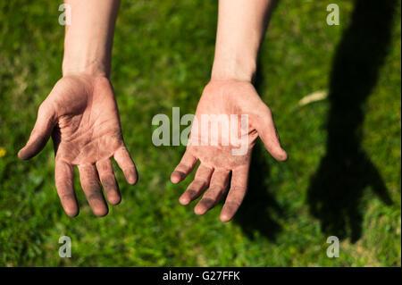 Une jeune femme est montrant de ses mains sales couvert de saleté du jardinage Banque D'Images