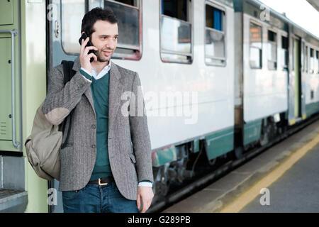 Homme debout sur le téléphone appelant attendant le train dans une gare platform Banque D'Images
