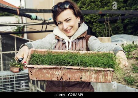 Jeune femme caucasienne joyeuse avec pot de ciboulette dans le jardin. Thème jardinage de saison. Chauffeur particulier Banque D'Images
