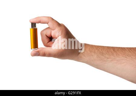 Un petit lecteur flash USB d'or tenu entre les doigts, isolé sur fond blanc Banque D'Images
