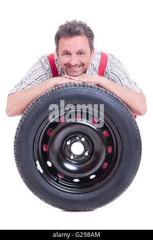Smiling mechanic resting head on tire isolé sur fond blanc Banque D'Images