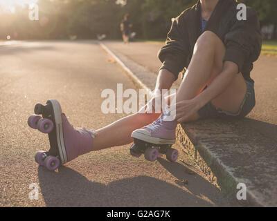 Une jeune femme est assise sur le sol et met sur patins à dans le parc au coucher du soleil Banque D'Images