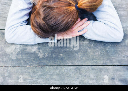 Une triste jeune femme avec sa tête reposant sur ses mains à une table dans le parc Banque D'Images