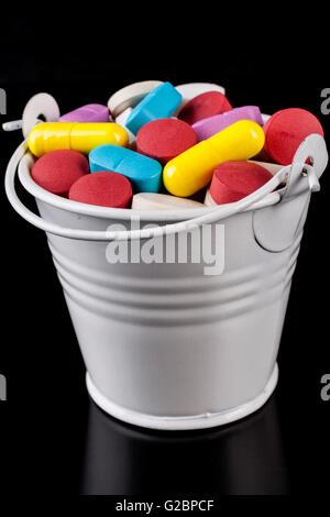 Comprimés de couleur de la médecine dans une benne blanc isolé sur fond noir Banque D'Images