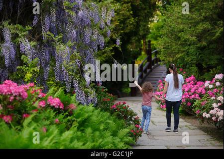 Mère et fille sur une promenade dans un jardin japonais. La femme tenant la main d'une petite fille. Ils marchent Banque D'Images