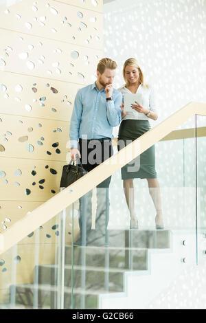Jeune couple sur l'escalier in modern office Banque D'Images