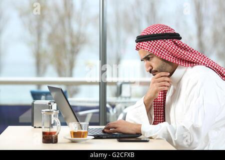 Vue latérale d'un arabe saoudien inquiet travaillant avec un ordinateur portable dans un intérieur avec la terrasse Banque D'Images