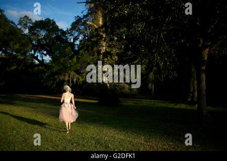 Femme en robe rose marchant sur pelouse, vue arrière Banque D'Images