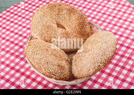 Round Bagels sésame dans le panier sur la table rouge Banque D'Images