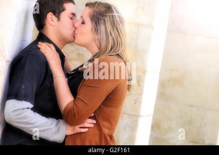 Les amoureux romantique robes noires et brunes s'embrasser dans un parc à l'extérieur des colonnes Banque D'Images