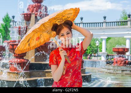 Belle asiatique fille en robe rouge traditionnelle chinoise avec parapluie en bambou près de la fontaine Banque D'Images