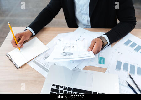 Close-up of hands holding documents et prendre des notes au bureau Banque D'Images