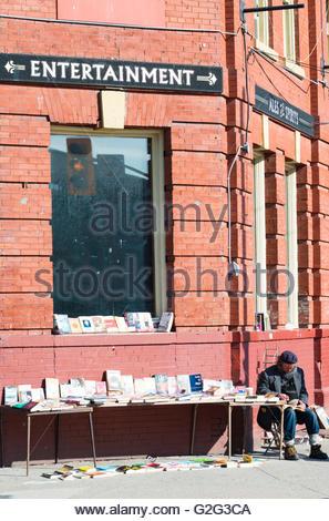 Vieil homme vendant des livres au quartier des spectacles au centre-ville de Toronto. Scènes quotidiennes Banque D'Images