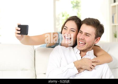 Le mariage ou le couple de rire et de prendre un téléphone avec selfies assis sur un canapé à la maison Banque D'Images