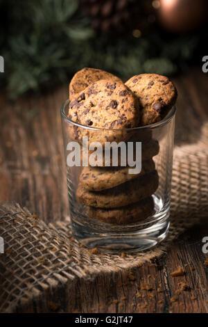 Des biscuits aux brisures de chocolat dans un verre sur une table en bois rustique.