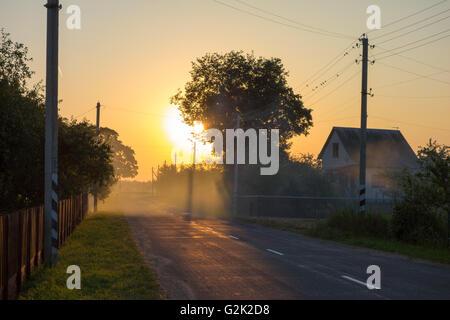 Coucher de soleil sur le village dans la brume Banque D'Images