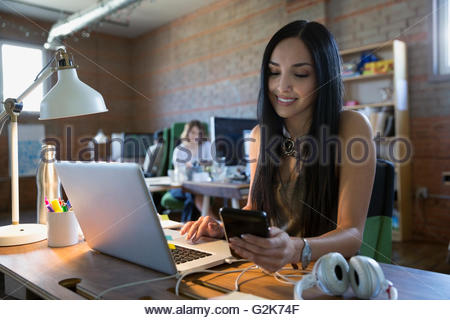 Creative businesswoman texting with cell phone at laptop in office Banque D'Images