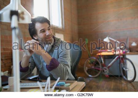 Pensive designer avec écouteurs at desk in office Banque D'Images